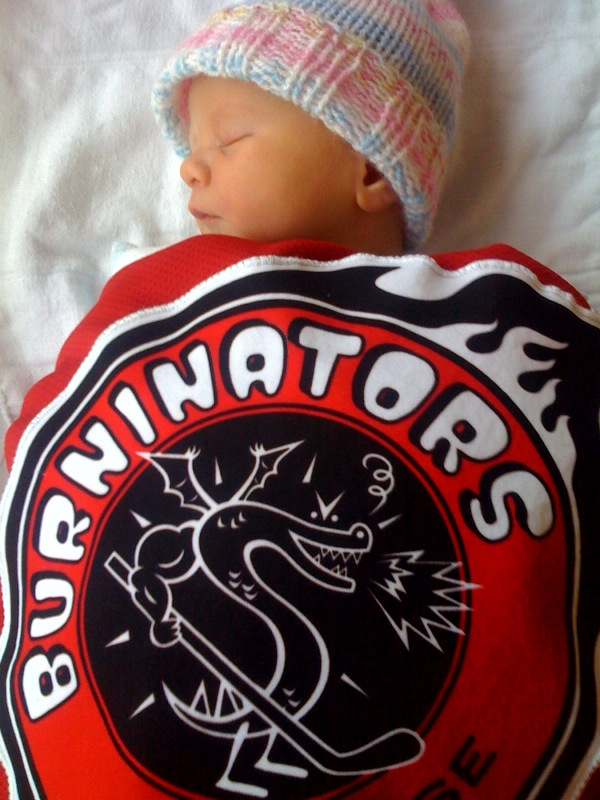 Only a day old and she's trying to wear Mommy's hockey jersey.
